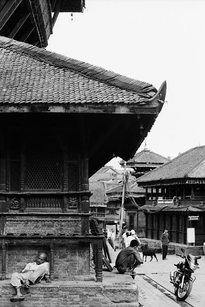 Man snoozing under eaves of Hindu temple