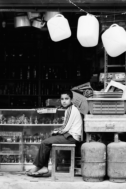 Boy sitting in storefront