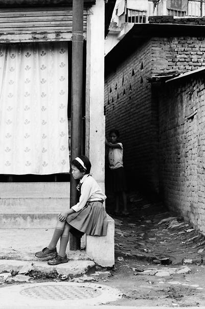 School girl sitting by roadside