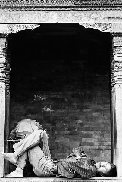 Man sleeping between wooden pillars