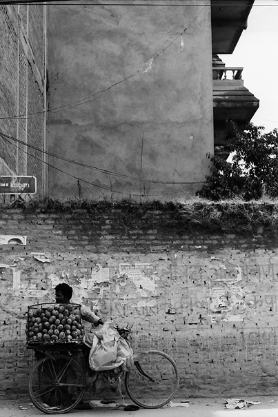 Mango seller standing against wall