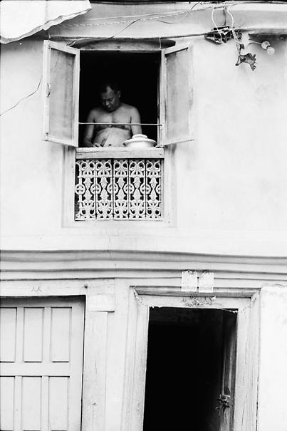 2階の窓辺で料理する男
