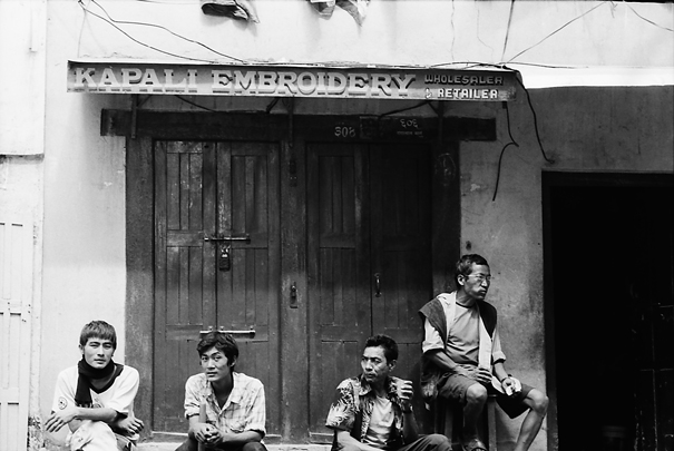 Men hanging out in front of closed store