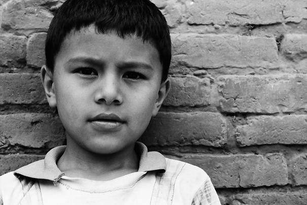 煉瓦造りの壁の前に立つ男の子