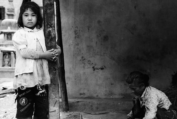 木造の柱を抱える女の子