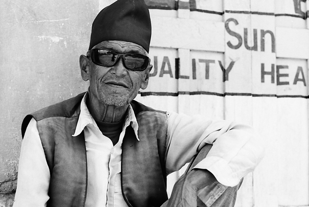 Old man wearing sunglasses and Bhadgaunle Topi