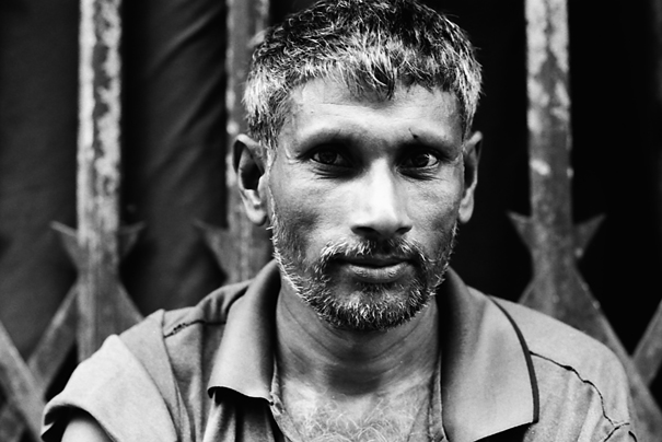 Man With Gray Whiskers Sitting In Front Of The Shutter (Bangladesh)