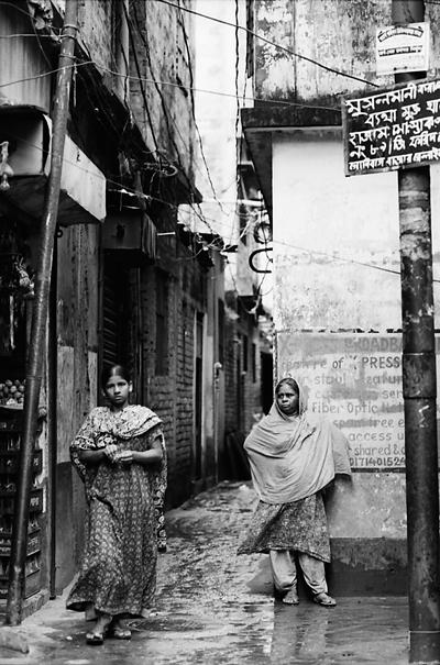 Two Women At The Entrance Of A Lane (Bangladesh)