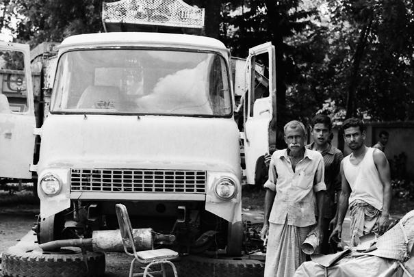 トラックの横に立つ男たち