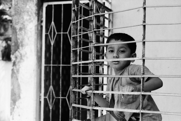 Boy on other side of lattice
