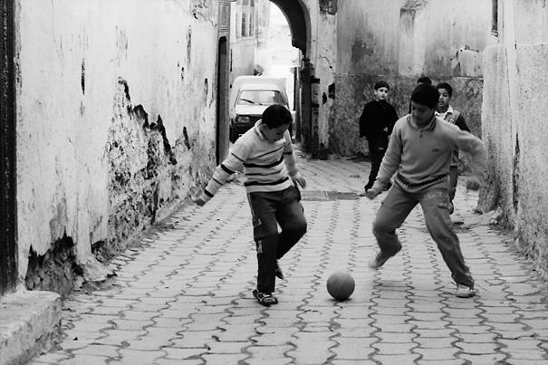 路地でサッカーをする男の子たち