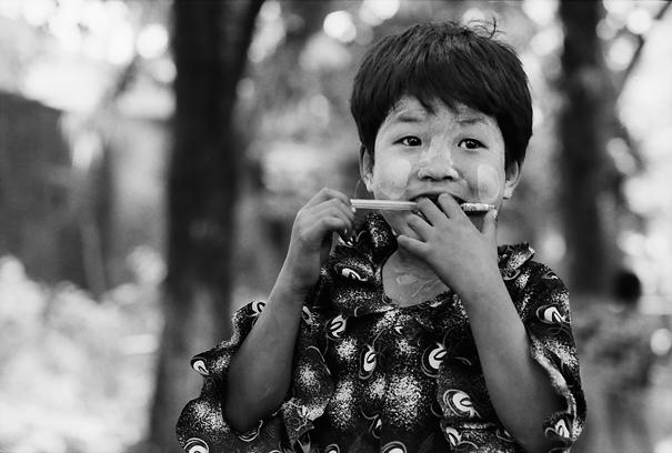Girl clutching pen in teeth