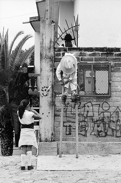 Girl watching boy attaching stilts