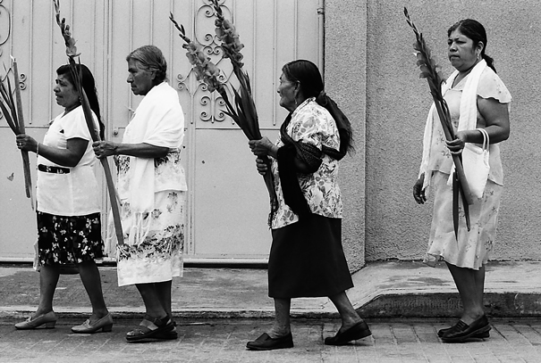 蝋燭と花を手に歩く女性たち