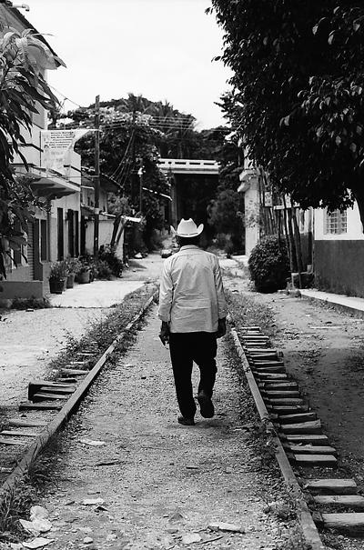 廃線の上を歩く男