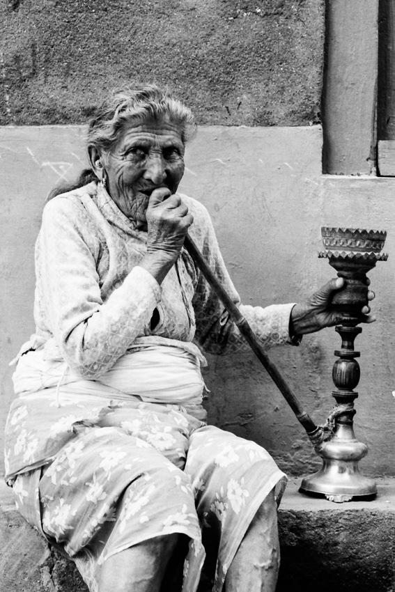 Older woman smoking water pipe under eaves