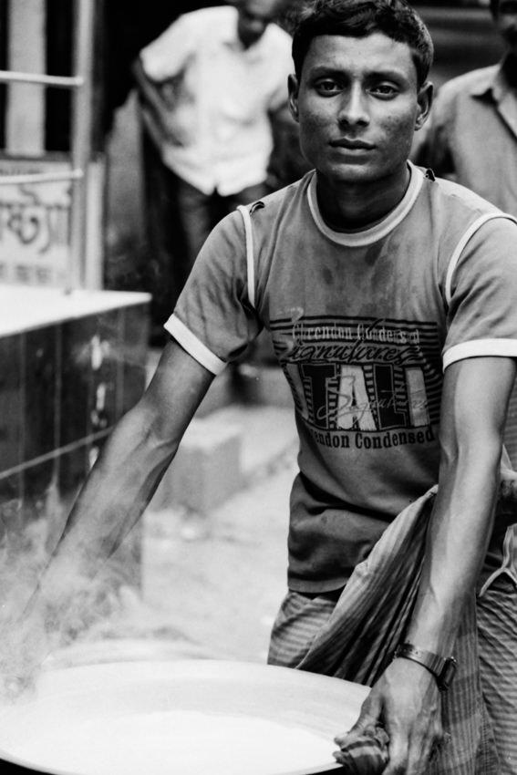 湯気が立ち上がる鍋を運ぶ男