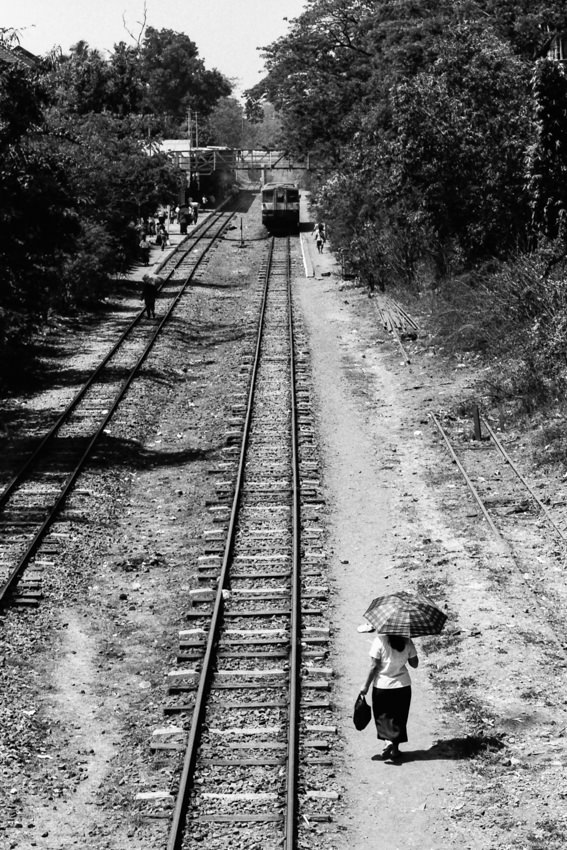 Woman with umbrella standing next to railroad