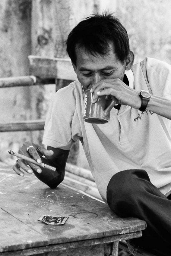 葉巻を吸いながらコーヒーを飲む男
