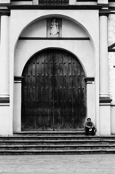 閉じられた扉の前にすわる男