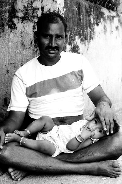 膝の上に赤ん坊を載せたお父さん