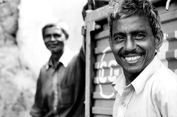 トラックの横で微笑む男