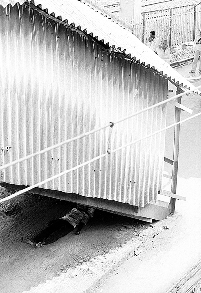Man sleeping under stairway