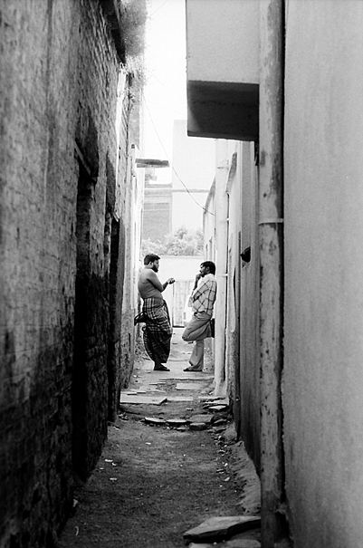 Two Men Discussing In The Back Street (India)