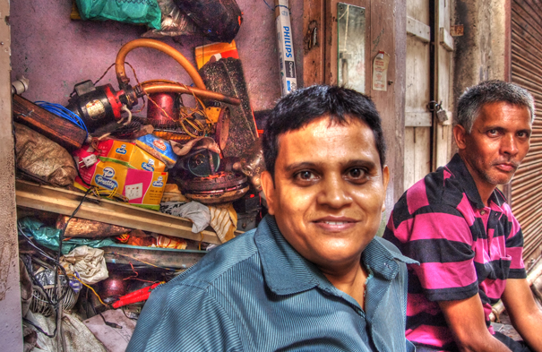 Two Men In Front Of A Junkyard (India)