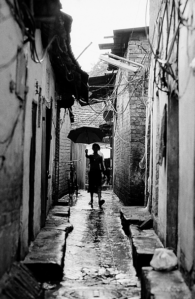 Silhouette With An Umbrella In The Lane (India)