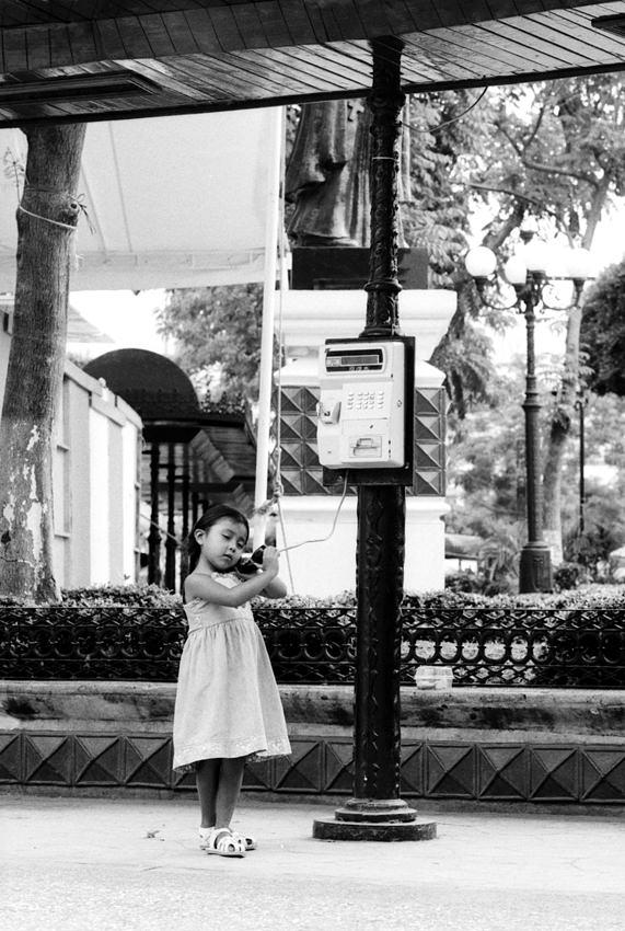 公衆電話で電話する女の子