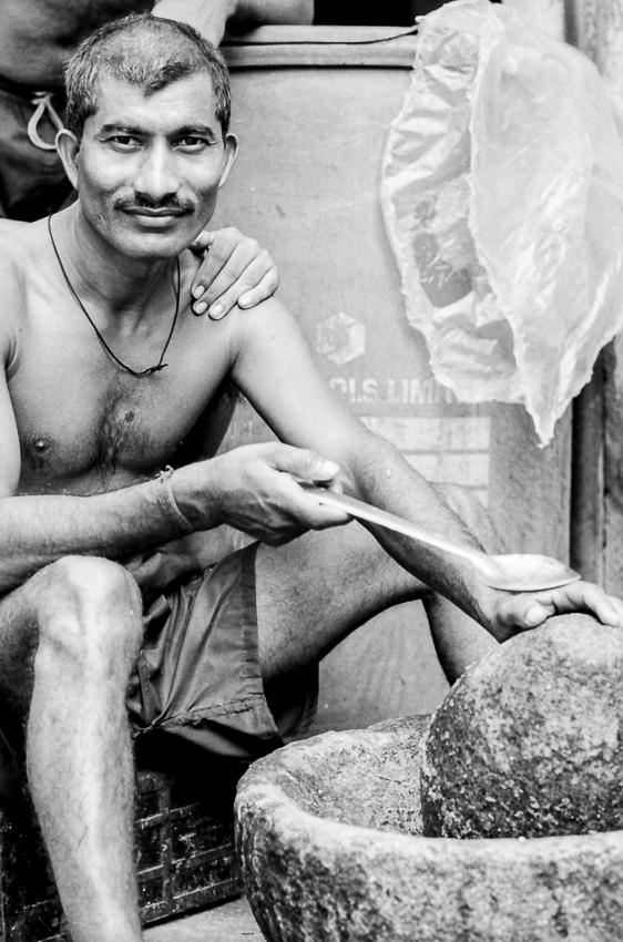 Man crushing spices in mortar