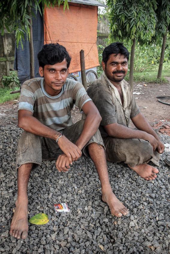 Men sitting on gravel