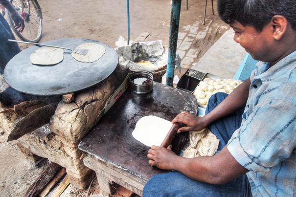 Man cooking Roti