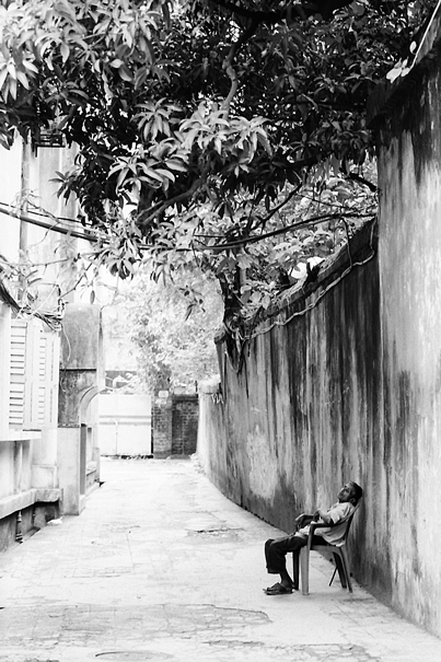 通路に腰掛けた男