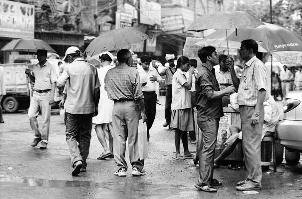 Men standing talking under umbrella