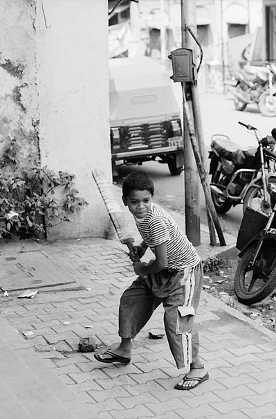 Boy Holding A Bat On The Sidewalk (India)