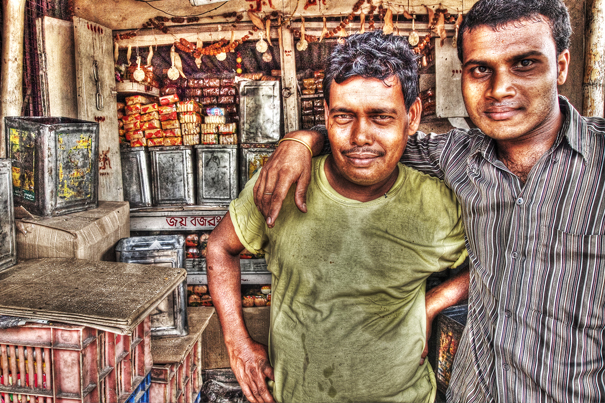 Two Men Standing Together In A Shop (India)