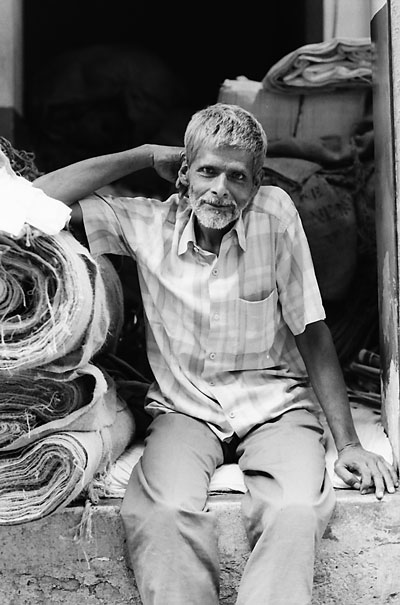 Man Sitting Beside Rolled Textiles (India)
