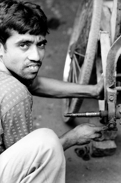 Man repairing cycle rickshaw