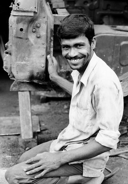 Man smiling beside car body