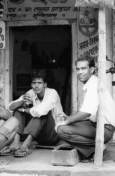 Men Relaxing  In A Storefront (India)