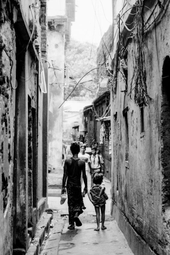 路地を歩く男と女の子の後ろ姿