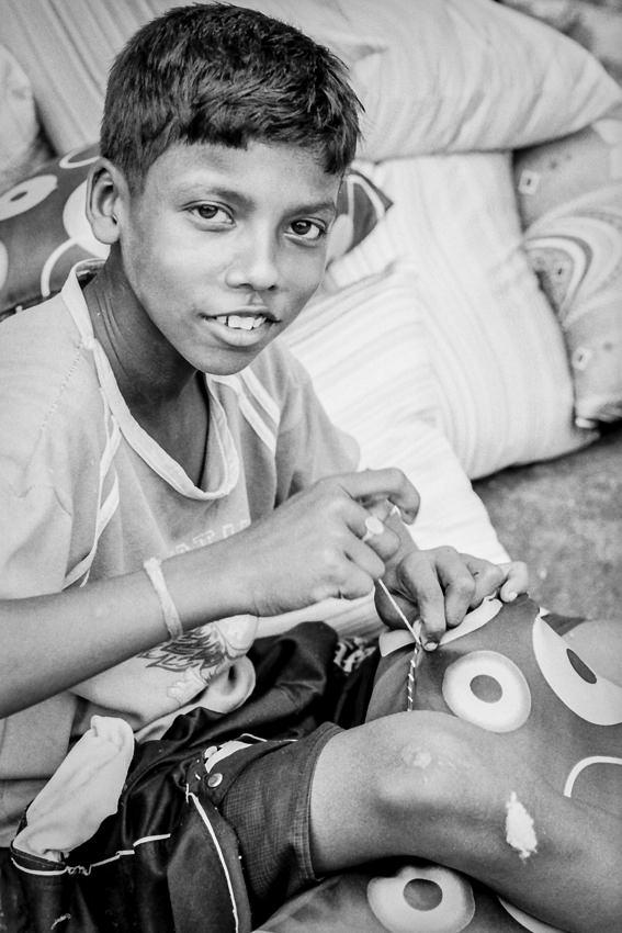 クッションを縫い合わせる男の子