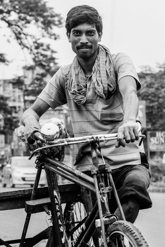 自転車で荷を運ぶ男