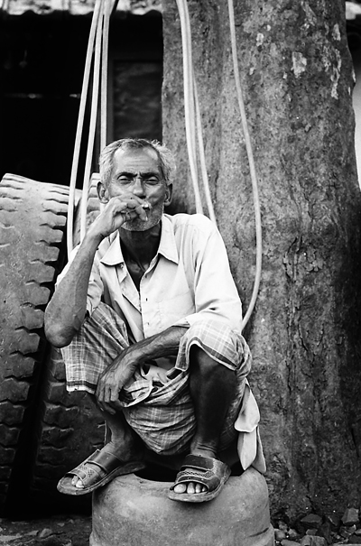 Smoking Man On The Old Tire (India)