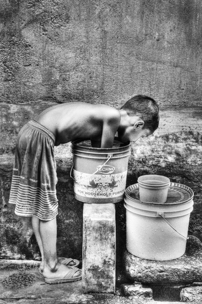Boy putting hands into bucket