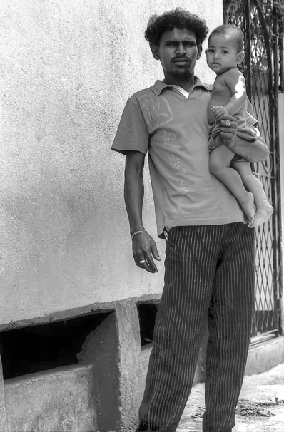Father And His Baby Standing Against The Wall (Sri Lanka)