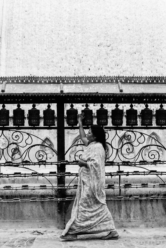 Woman turning around prayer wheels