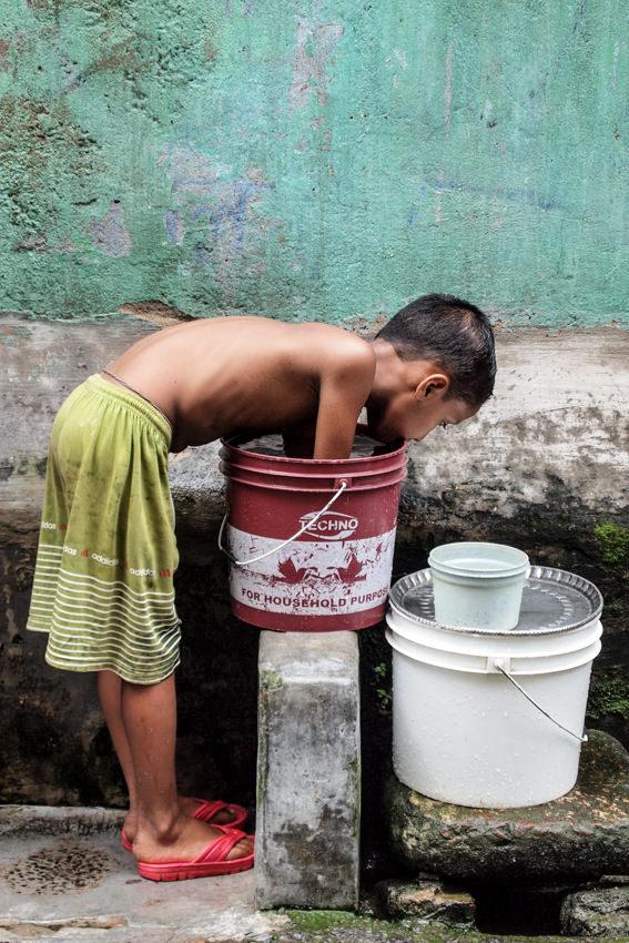 Boy putting hands into bucket